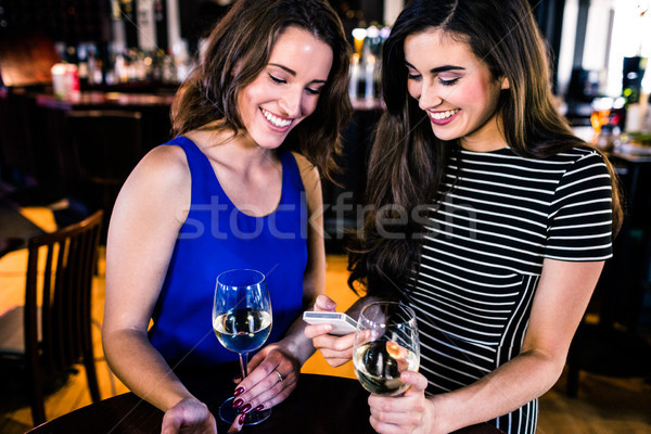 Friends texting and having a glass of wine Stock photo © wavebreak_media