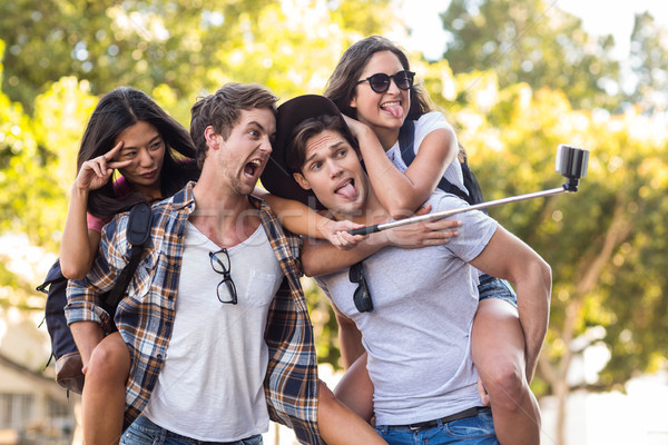 Hip men giving piggy back to their girlfriends and taking selfie Stock photo © wavebreak_media