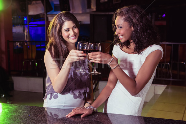 Young women toasting wine glasses at bar counter Stock photo © wavebreak_media