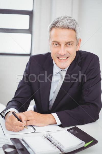 Happy businessman writing in spiral notebook Stock photo © wavebreak_media