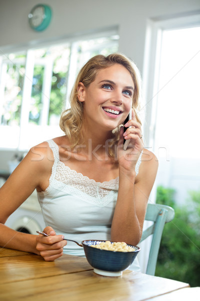 Young woman talking on mobile phone while having breakfast at ho Stock photo © wavebreak_media