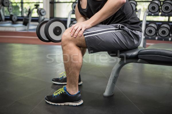 Férfi ül pad emel súlyzók tornaterem Stock fotó © wavebreak_media