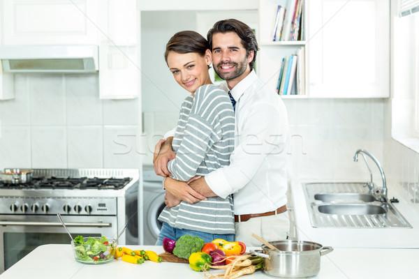 Couple embracing while preparing food in kitchen Stock photo © wavebreak_media