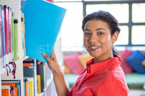 Glimlachend leraar boek boekenplank bibliotheek portret Stockfoto © wavebreak_media