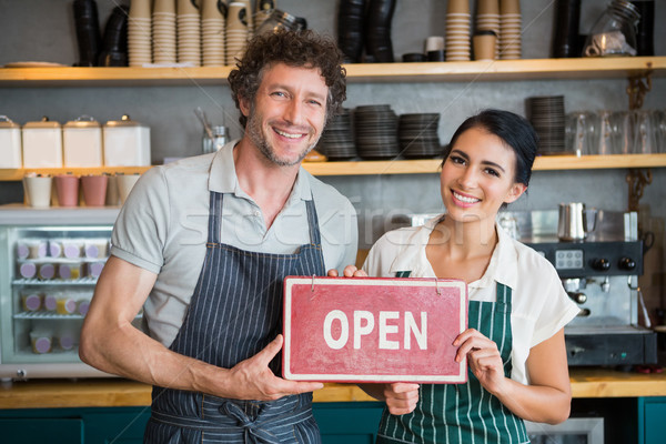Portrait of waiter and waitress holding open signboard Stock photo © wavebreak_media