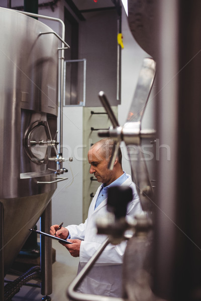 Mature manufacturer standing amidst storage tanks at brewery Stock photo © wavebreak_media