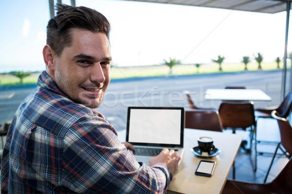 Człowiek za pomocą laptopa kawiarnia portret uśmiechnięty komputera Zdjęcia stock © wavebreak_media