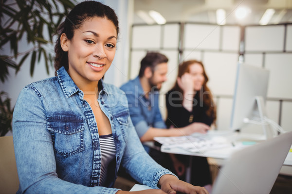 Sorridente criador empresária usando laptop secretária retrato Foto stock © wavebreak_media