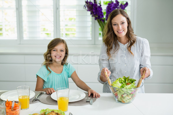 Portrait of smiling mother and daughter mixing bowl of salad in kitchen Stock photo © wavebreak_media