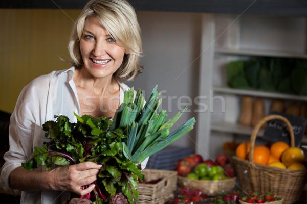 Portrait of female costumer holding fresh vegetables in organic section Stock photo © wavebreak_media