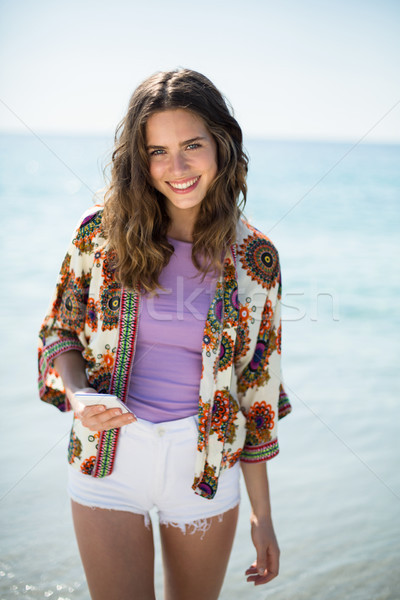 Young woman smiling while standing on seashore Stock photo © wavebreak_media
