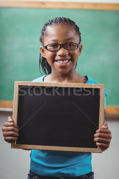 Smiling pupil holding chalkboard in a classroom  Stock photo © wavebreak_media