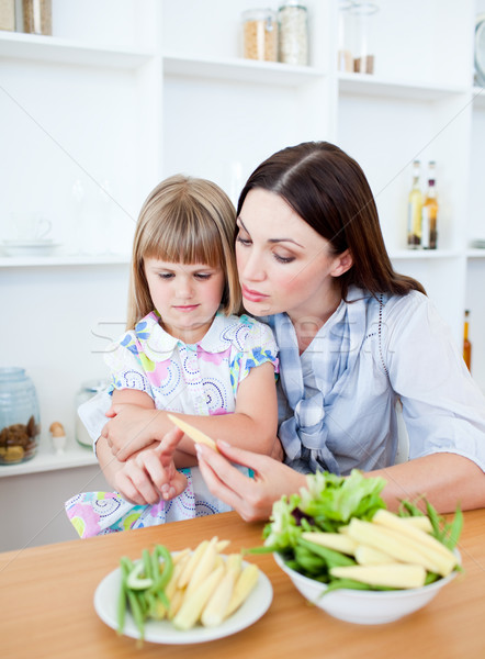 Dissatisfied little girl eating vegetables with her mother Stock photo © wavebreak_media