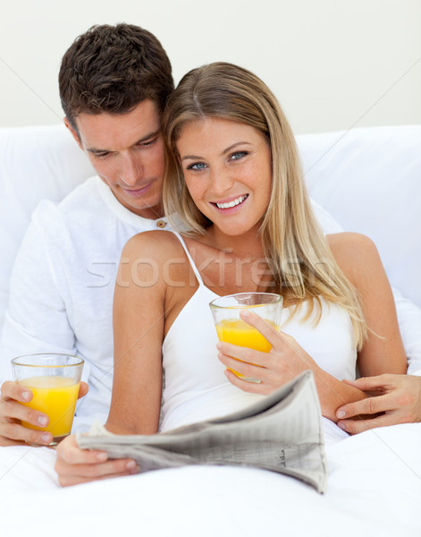 Loving couple reading a newspaper and drinking orange juice  Stock photo © wavebreak_media