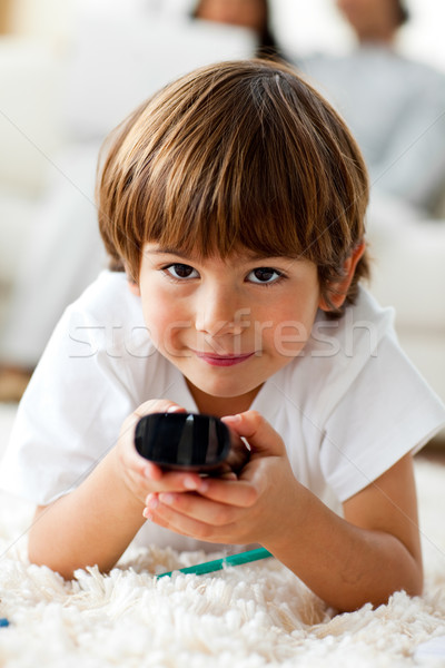 Smiling little boy holding a remote lying on the floor  Stock photo © wavebreak_media