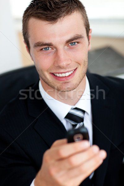 Stock photo: Young businessman holding mobile phone in office