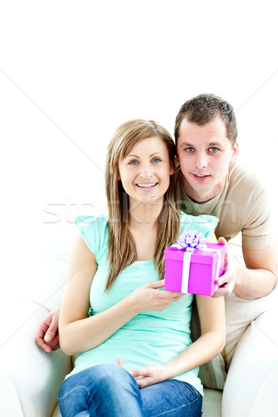 Young boyfriend giving a present to his glowing girlfriend against white background  Stock photo © wavebreak_media