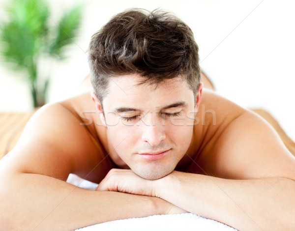 Stock photo: Portrait of an attractive man lying on a massage table in a spa center
