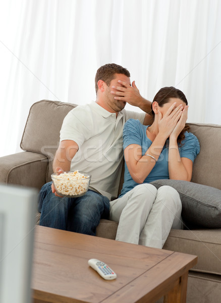 Lovely couple hiding their face from a horror movie sitting in the living-room at home Stock photo © wavebreak_media