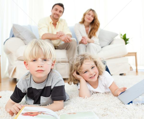 Childrens reading books in the living rooms Stock photo © wavebreak_media