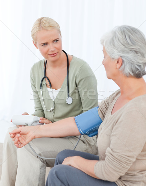Lovely doctor taking the blood pressure of her patient Stock photo © wavebreak_media