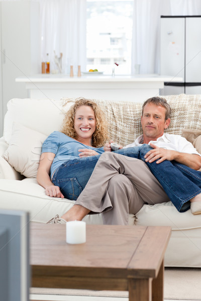 Lovers watching tv in the living room at home Stock photo © wavebreak_media