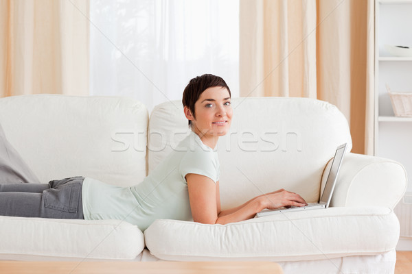 Short-haired woman with a laptop while looking at the camera Stock photo © wavebreak_media