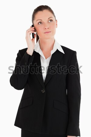 Pretty woman in suit on the phone while standing against a white background Stock photo © wavebreak_media