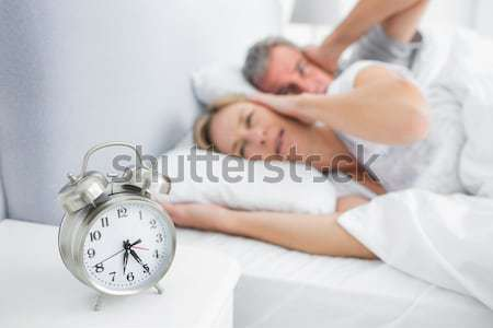 Good looking red-haired woman lying in bed not wanting to hear the alarm clock Stock photo © wavebreak_media