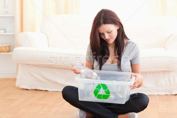 Cute woman putting bottles in a recycling box in her home Stock photo © wavebreak_media