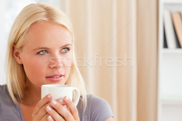 женщину сидят диван Кубок чай Сток-фото © wavebreak_media