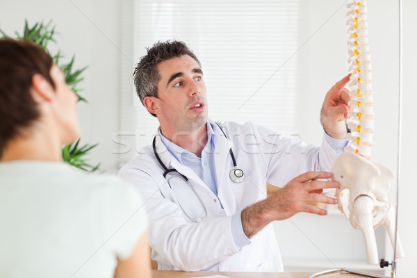 Doctor showing a woman a part of a spine in a room Stock photo © wavebreak_media