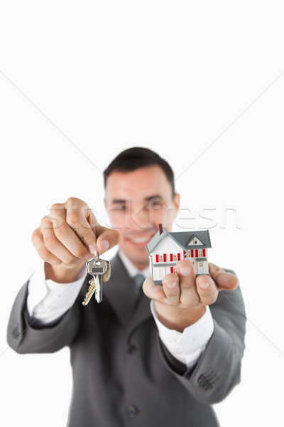 Miniature house and keys being presented by male estate agent against a white background Stock photo © wavebreak_media