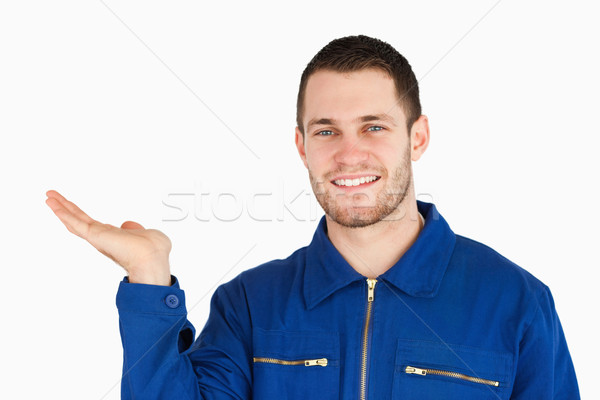 Smiling young mechanic presenting something in his palm against a white background Stock photo © wavebreak_media