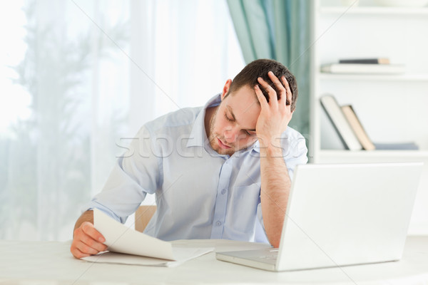 Stock photo: Young businessman reading an alarming letter