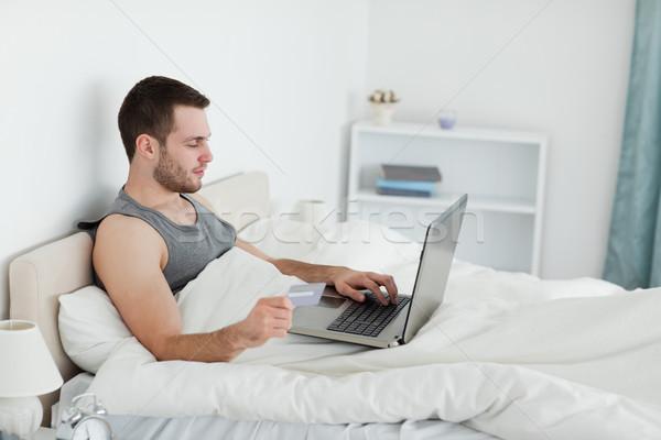 Yakışıklı adam çevrimiçi yatak odası bilgisayar mutlu ev Stok fotoğraf © wavebreak_media
