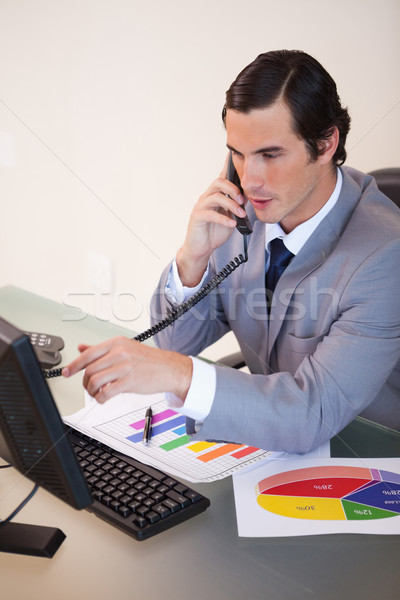 Stock photo: Young businessman talking on the phone while working on statistics