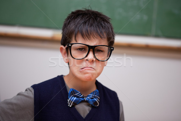 Grumpy schoolboy posing in a classroom Stock photo © wavebreak_media