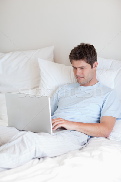 Man surfing the internet in his bed Stock photo © wavebreak_media