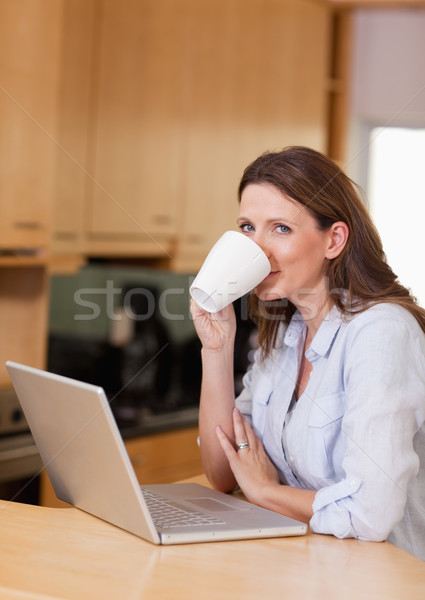 Stock photo: Woman taking a sip of coffee next to her laptop
