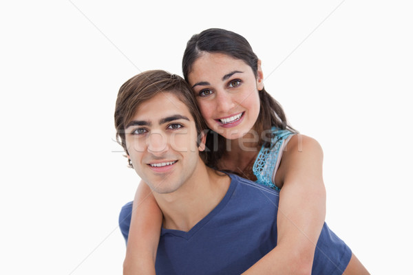 Stock photo: Man holding his girlfriend on his back against a white background