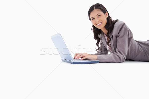 Side view of smiling woman lying while working on laptop against a white background Stock photo © wavebreak_media