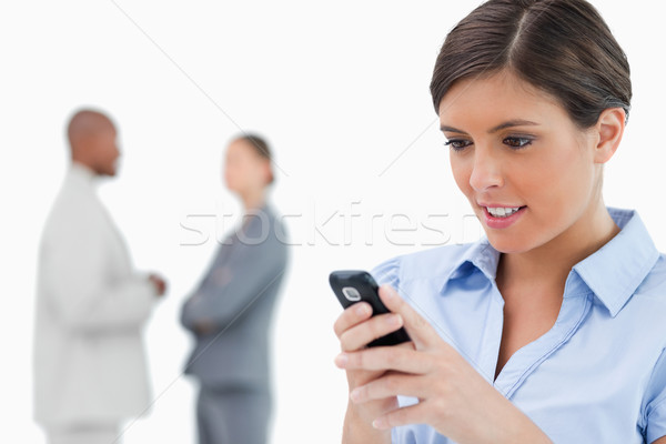 Businesswoman reading text message with associates behind her against a white background Stock photo © wavebreak_media