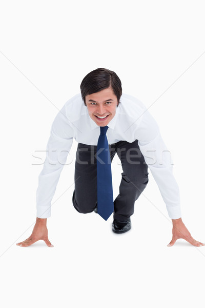 Smiling tradesman in sprinting position against a white background Stock photo © wavebreak_media