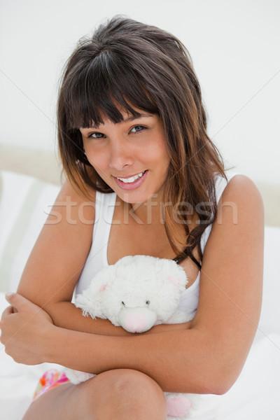 Fiatal nő ölel kicsi plüssmaci ül ágy Stock fotó © wavebreak_media