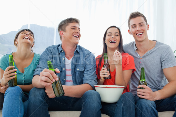 A laughing group of friends sitting with popcorn and beer as they have fun together Stock photo © wavebreak_media