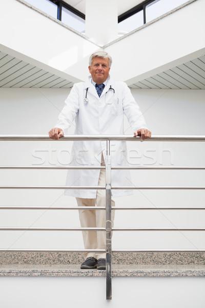 Smiling doctor in labcoat leaning against rail in hospital corridor Stock photo © wavebreak_media
