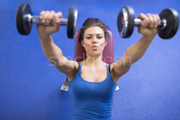 Black-haired woman energetically lifting weights Stock photo © wavebreak_media