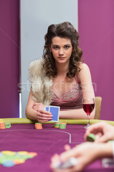Woman sitting holding cards at the table Stock photo © wavebreak_media