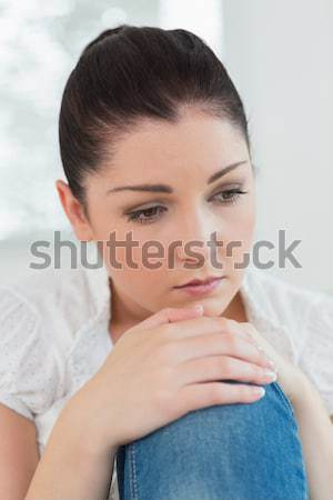 Thoughtful woman sitting on the couch in a living room and looking sad Stock photo © wavebreak_media